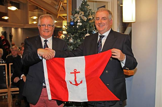 HYC outgoing Commodore Berchmans Gannon (left) presents the office holder's burgee to incoming Commodore Joe McPeake